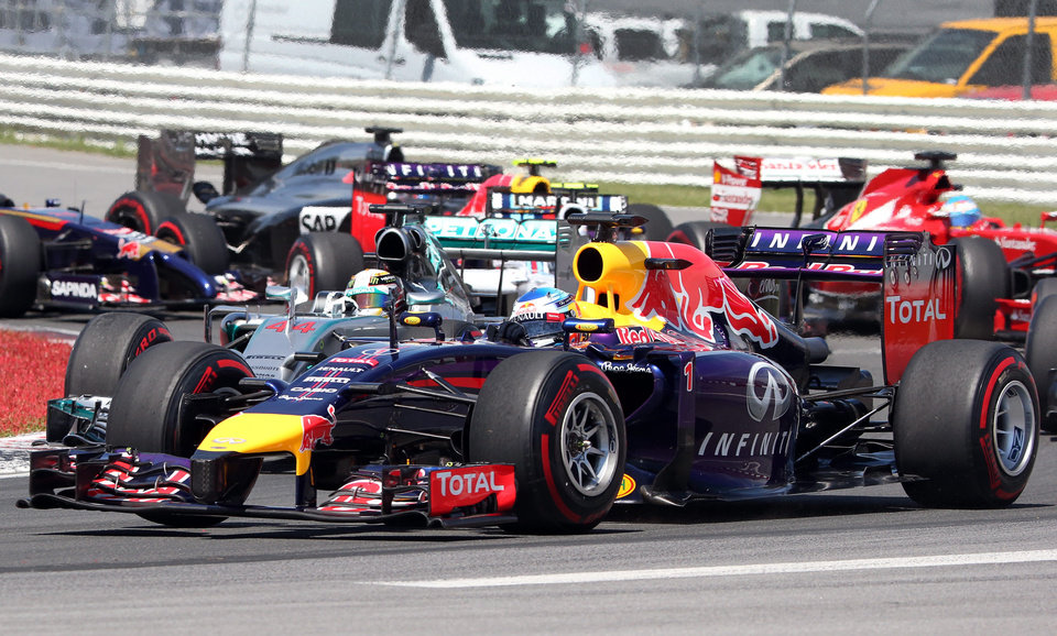Photo - Red Bull driver Sebastian Vettel from Germany, foreground, passes Mercedes driver Lewis Hamilton from Great Britain, at the start of the Canadian Grand Prix Sunday, June 8, 2014 in Montreal. (AP Photo/The Canadian Press, Tom BNoland)