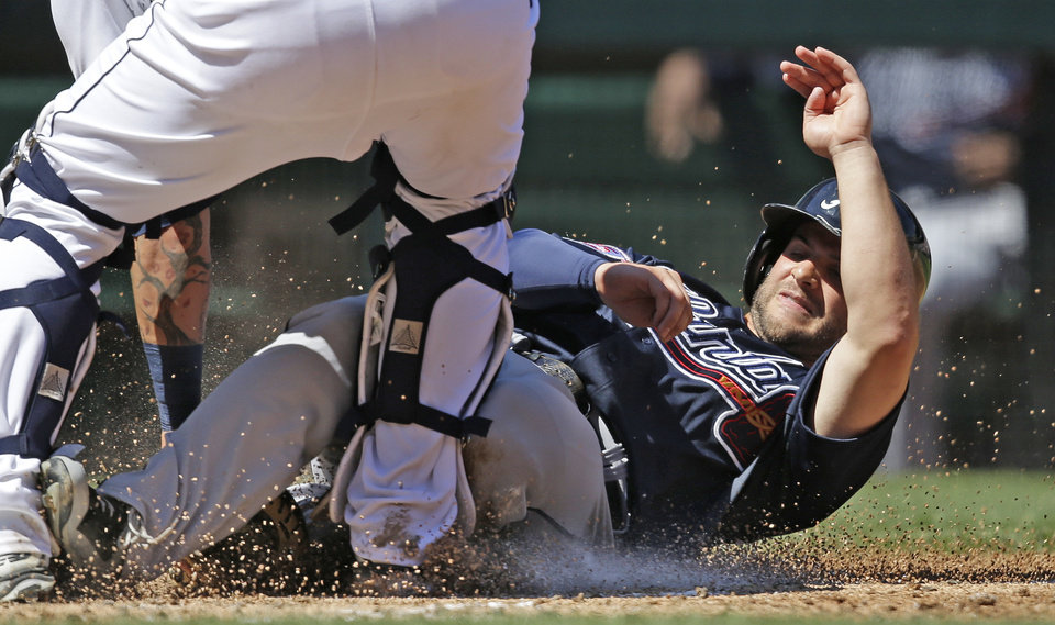 Photo - Atlanta Braves' Tommy La Stella is tagged out at home after following in two teammates that scored ahead of him on a double by Freddie Freeman against the Seattle Mariners in the third inning of a baseball game Wednesday, Aug. 6, 2014, in Seattle. (AP Photo/Elaine Thompson)
