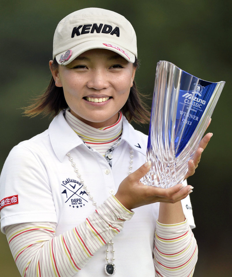 Photo - Taiwan's Teresa Lu poses with her trophy after she won the Mizuno Classic golf tournament in Shima, Mie prefecture, western Japan Sunday, Nov. 10, 2013. (AP Photo/Kyodo News) JAPAN OUT, MANDATORY CREDIT