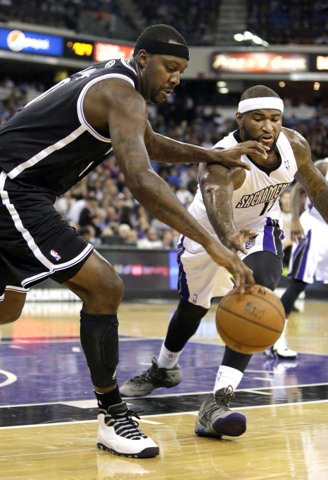 Photo - Brooklyn Nets center Andray Blatche, left, and Sacramento Kings center DeMarcus Cousins scramble for the ball during the first quarter of an NBA basketball game in Sacramento, Calif., Wednesday, Nov. 13, 2013. (AP Photo/Rich Pedroncelli)