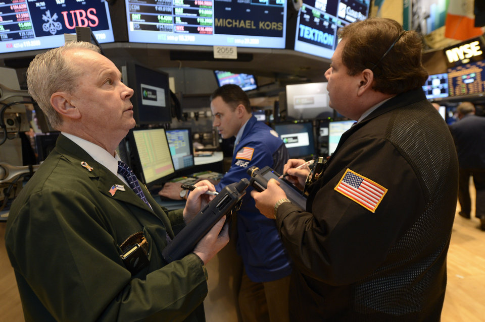 Photo - James Riley, left, of Dag Securities works  on the floor of the New York Stock Exchange, Wednesday, Feb. 13, 2013 in New York. (AP Photo/Henny Ray Abrams)