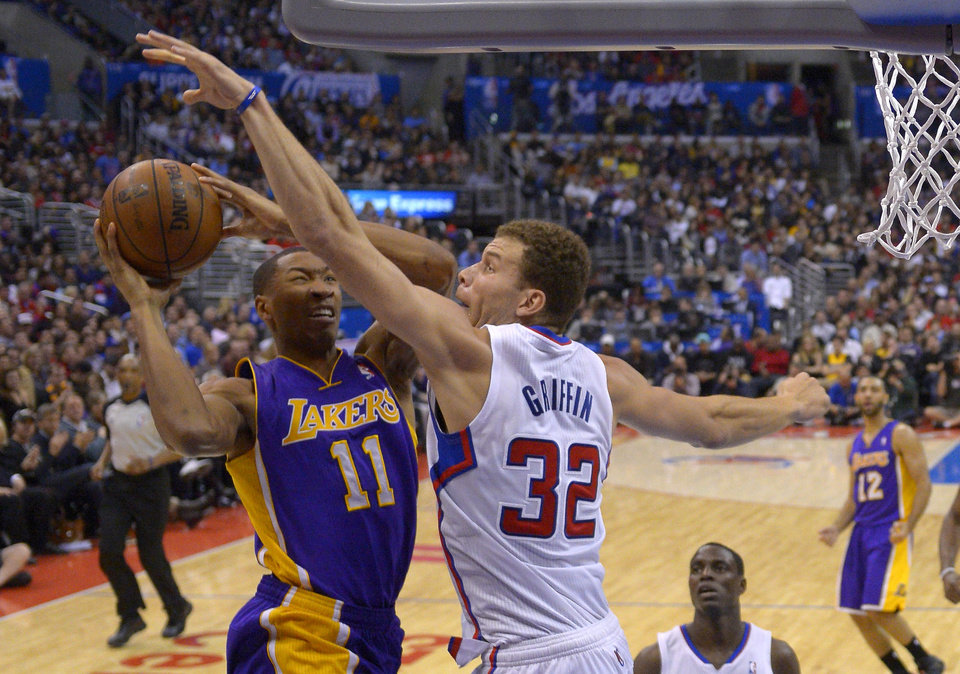 Photo - Los Angeles Lakers guard Wesley Johnson, left, puts up a shot as Los Angeles Clippers forward Blake Griffin defends during the first half of an NBA basketball game, Friday, Jan. 10, 2014, in Los Angeles. (AP Photo/Mark J. Terrill)