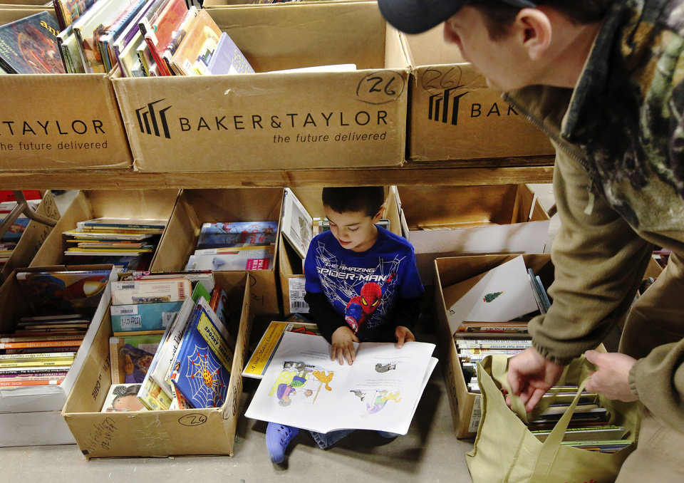 Caleb Mackey, 6, finds a quiet spot under a table to read some of the books he's picked out. He came to the sale with his mom, dad, shown at right,  and a brother. Several thousand bibliophiles and bargain hunters crowded into Oklahoma Expo Hall at State Fair Park on Saturday, Feb. 23, 2013,  in a quest to find reading material  at deeply discounted  prices.  Friends of the Metropolitan Library System is holding their much-anticipated annual book sale this weekend. The sale continues Sunday from 9 a.m. to 5:30 p.m.   Photo by Jim Beckel, The Oklahoman