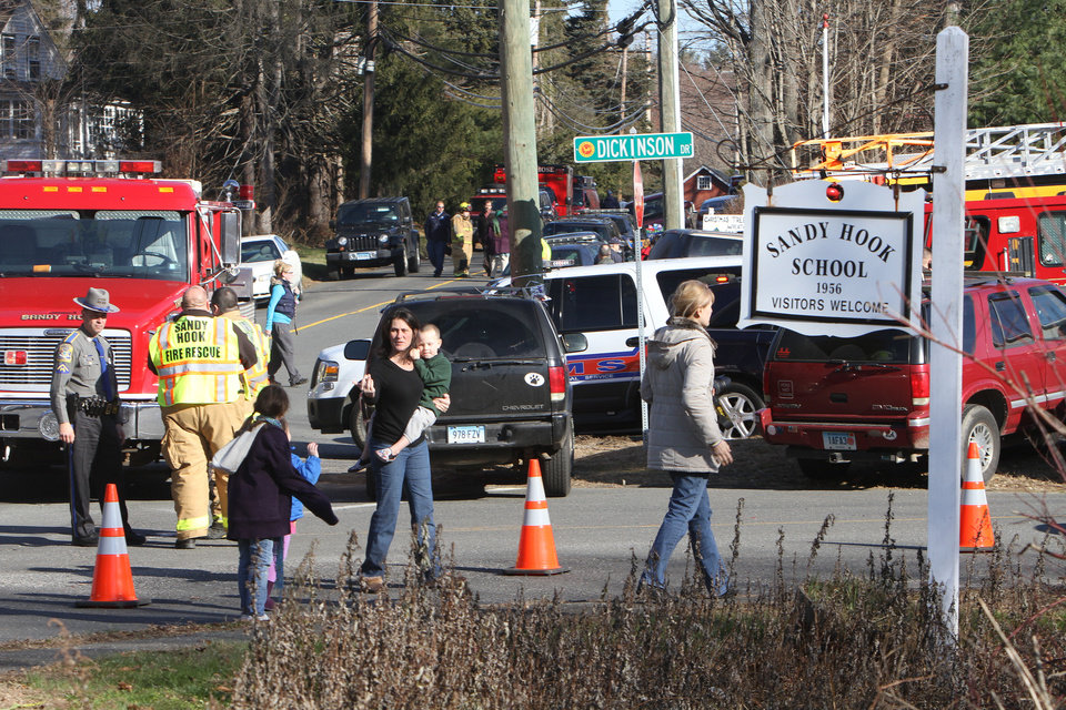 Photo - Parents walk away with their children from Sandy Hook Elementary School in Newtown, Conn. where authorities say a gunman opened fire, leaving 27 people dead, including 20 children, Friday, Dec. 14, 2012. (AP Photo/The Journal News, Frank Becerra Jr.) MANDATORY CREDIT, NYC OUT, NO SALES, TV OUT, NEWSDAY OUT; MAGS OUT ORG XMIT: NYWHI112