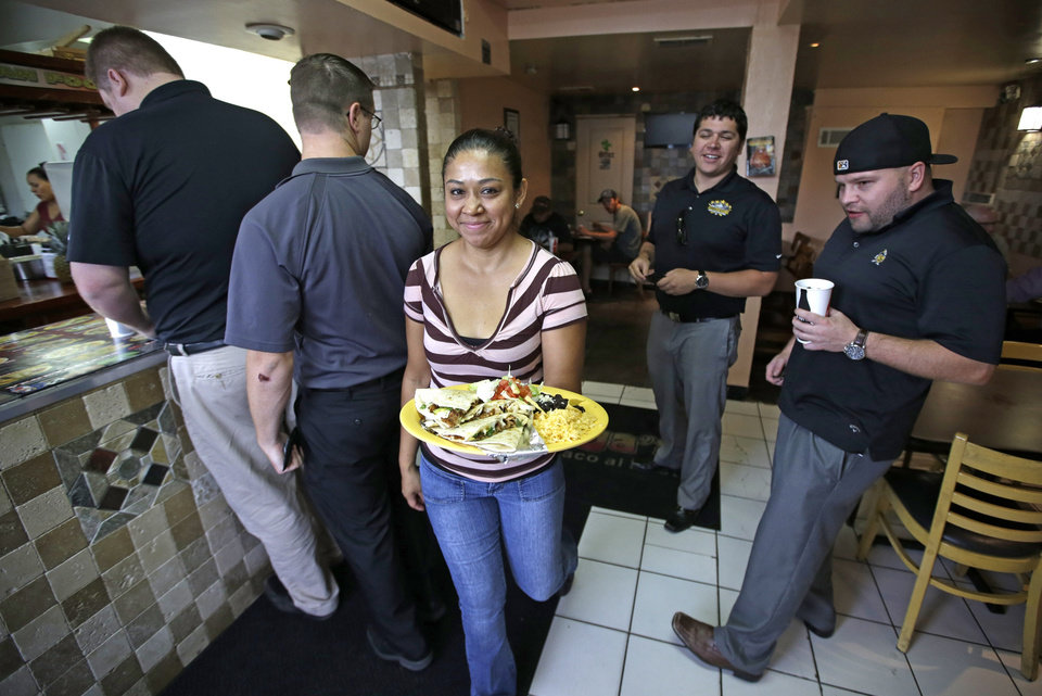Photo - In this July 29, 2014, photo, waitress Maribel Albanez delivers food to patrons at Chunga's Mexican Grill, in Salt Lake City. The hunt for a taste of Mexico City brings diners near a highway overpass in a neighborhood known for tire shops and tacos. (AP Photo/Rick Bowmer)