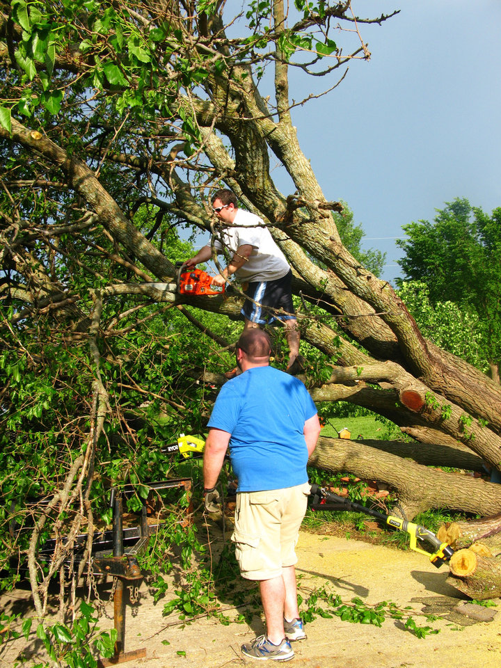 Judy Pendergraft's grandsons, Andrew Peery, in the tree, and Jeremy Peery help her cut down a fallen tree in her driveway in the Hidden Valley addition in southeast Edmond. Photo by Lillie-Beth Brinkman