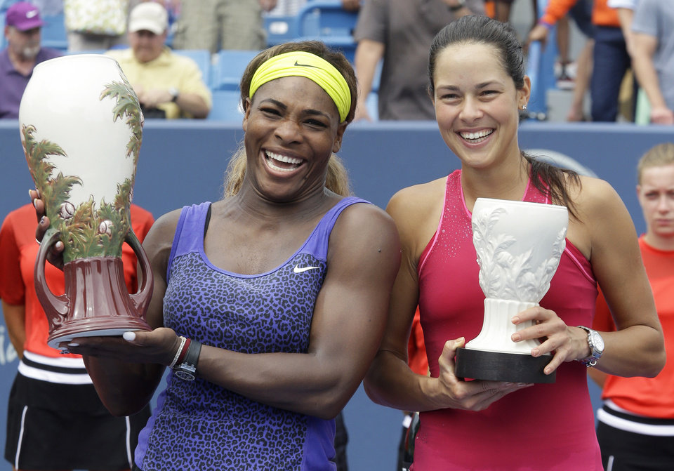 Photo - Serena Williams, left, and Ana Ivanovic, from Serbia, pose with their trophies after Williams defeated Ivanovic 6-4, 6-1, in the women's final match at the Western & Southern Open tennis tournament, Sunday, Aug. 17, 2014, in Mason, Ohio. (AP Photo/Al Behrman)