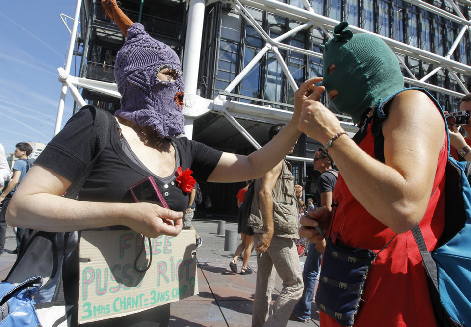 Photo -   Demonstrators adjust their masks during a demonstration in support of the Russian punk group Pussy Riot during a protest in Paris Friday Aug. 17, 2012. Three members of Pussy Riot were jailed in March and charged with hooliganism motivated by religious hatred after their punk performance against President Putin in Moscow's main cathedral. They are awaiting the verdict later Friday, Aug. 17, 2012. Banner reads: 3 minutes of song 3 years of jails.(AP Photo/Jacques Brinon)
