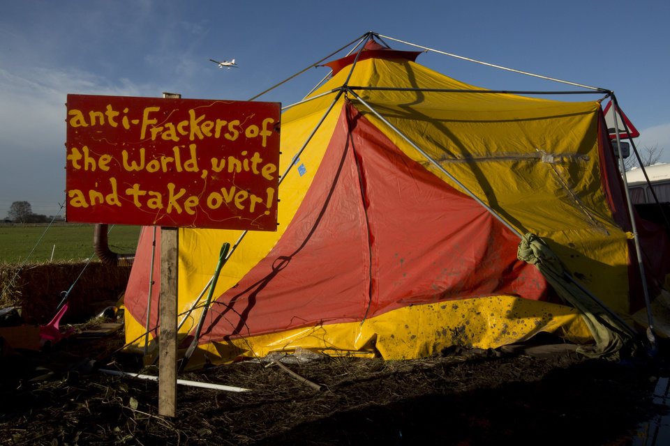 Photo - A sign is seen outside a tent in an anti-fracking protest camp by an exploratory drill site for the controversial gas extraction process at Barton Moss in Manchester, England, Monday, Jan. 13, 2014.  Councils that back