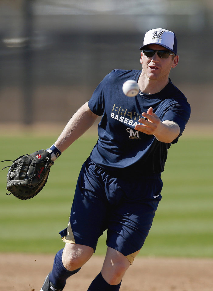 Photo - Milwaukee Brewers' Lyle Overbay tosses a ball to first base as a pitcher covers the base during Brewers spring training baseball practice, Monday, Feb. 17, 2014, in Phoenix. (AP Photo/Ross D. Franklin)