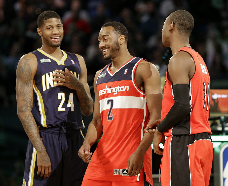 Photo - The winners of the slam dunk contest Paul George of the Indiana Pacers, John Wall of the Washington Capitals and Terrence Ross celebrate during the skills competition at the NBA All Star basketball game, Saturday, Feb. 15, 2014, in New Orleans. (AP Photo/Gerald Herbert)