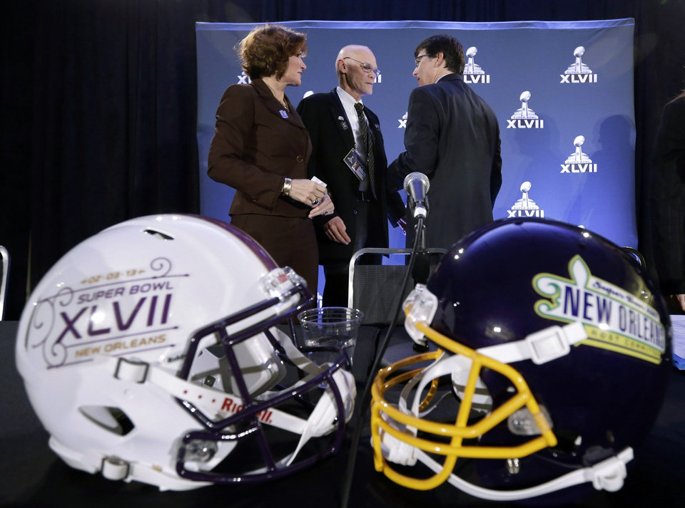 Photo - Political commentators Mary Matalin, left, and James Carville chat with Jay Cicero, president and CEO of the Greater New Orleans Sports Foundation, after speaking at an NFL football Super Bowl XLVII news conference on Monday, Jan. 28, 2013, in New Orleans. (AP Photo/Patrick Semansky)
