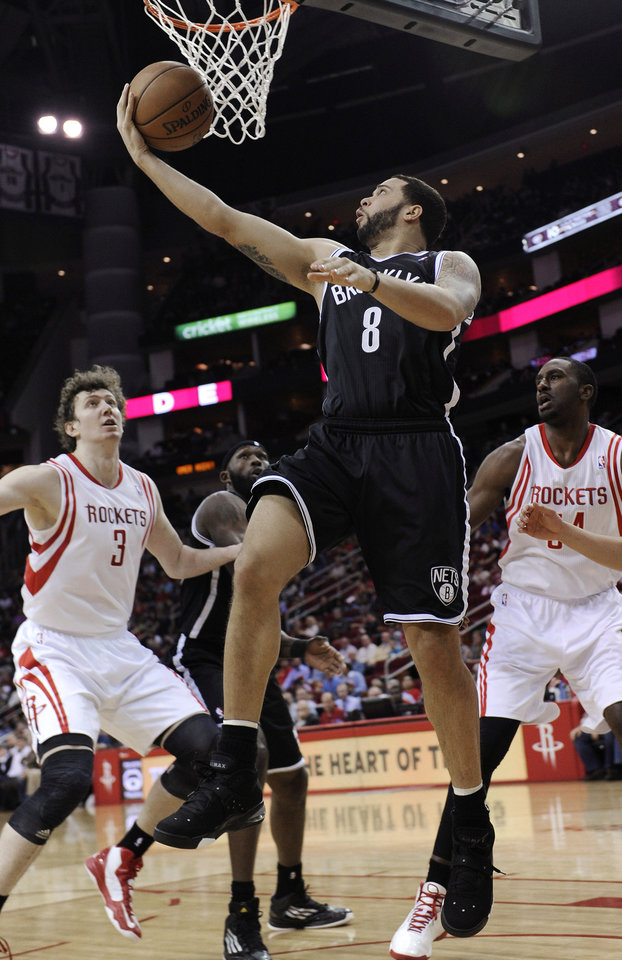 Brooklyn Nets' Deron Williams (8) goes up for a shot between Houston Rockets Omer Asik (3) and Patrick Patterson (54) in the first half of an NBA basketball game Saturday, Jan. 26, 2013, in Houston. (AP Photo/Pat Sullivan)