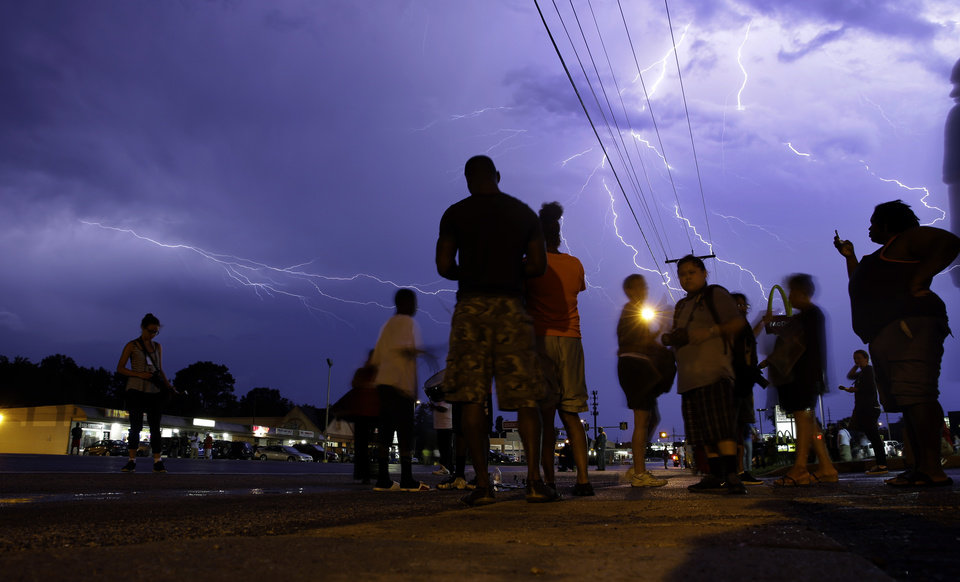 Photo - Protesters stand in the street as lightning fills the night sky Wednesday, Aug. 20, 2014, in Ferguson, Mo. A grand jury has begun hearing evidence as it weighs possible charges against the Ferguson police officer who fatally shot 18-year-old Michael Brown. (AP Photo/Jeff Roberson)