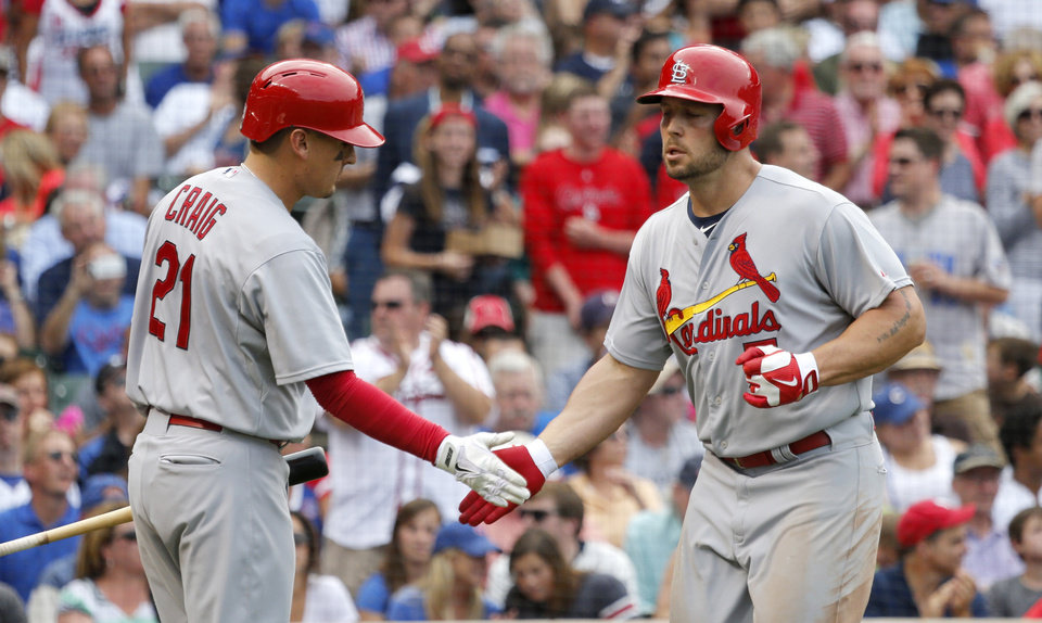 Photo - St. Louis Cardinals' Allen Craig (21) greets Matt Holliday outside the dugout after Holliday's home run off Chicago Cubs starting pitcher Travis Wood during the fifth inning of a baseball game Friday, July 25, 2014, in Chicago. (AP Photo/Charles Rex Arbogast)