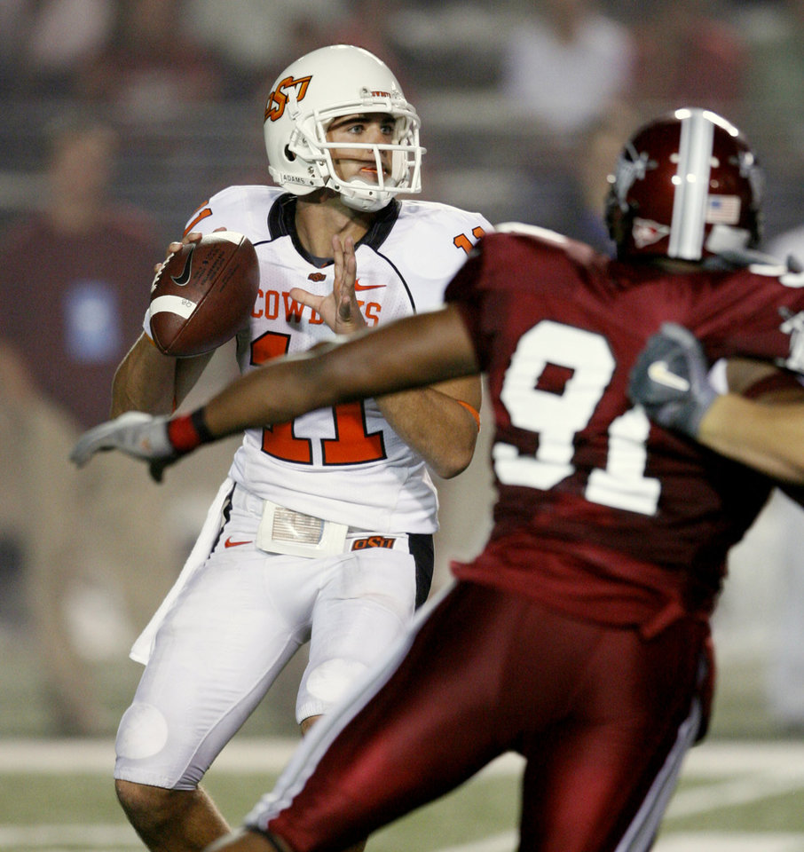 Quarterback Zac Robinson is rushed by Brandon Lang in first half action during the college football game between the Troy University Trojans and the Oklahoma State University Cowboys at Movie Gallery Veterans Stadium in Troy, Ala., Friday, September 14, 2007. BY STEVE SISNEY, THE OKLAHOMAN
