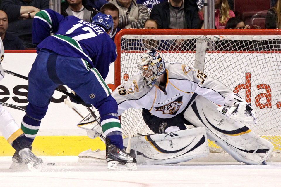 Nashville Predators' Pekka Rinne, right, of Finland, stops Vancouver Canucks' Ryan Kesler during the first period of an NHL hockey game in Vancouver, British Columbia, on Wednesday, Jan. 26, 2011. (AP Photo/The Canadian Press, Darryl Dyck)