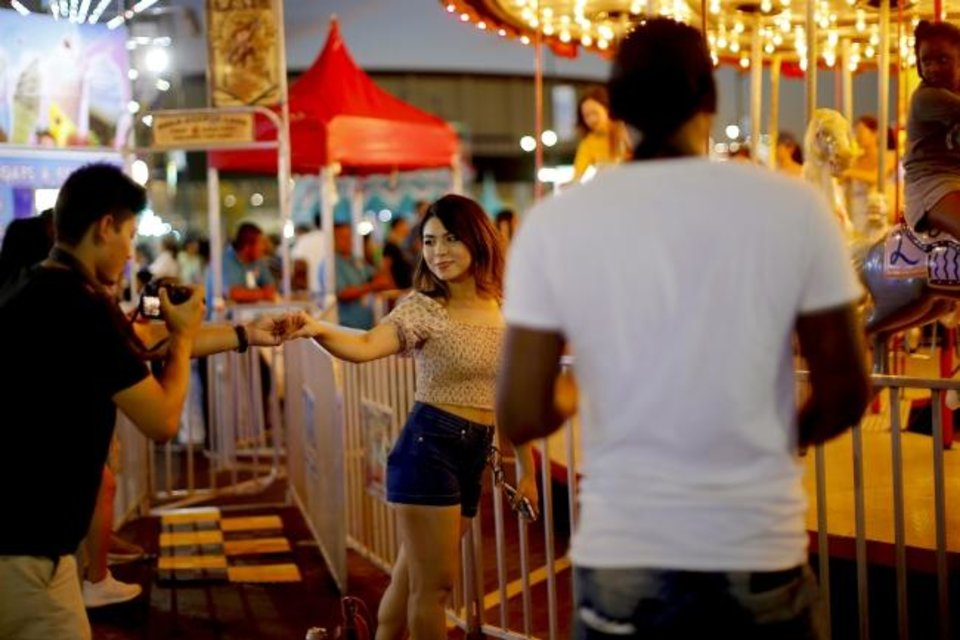 Photo -  Rajiv Maharjan takes a picture of Barsha Katwal in front of a merry-go-round at the Oklahoma State Fair. [Bryan Terry/The Oklahoman]