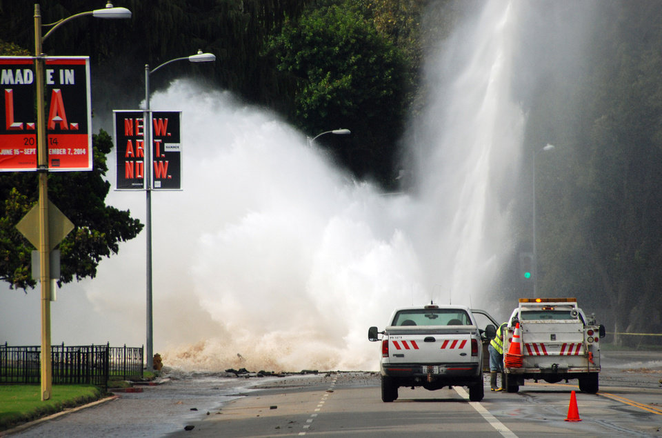 Photo - Water shoots in the air from a broken 30-inch water main under Sunset Boulevard, uphill from UCLA in the Westwood section of Los Angeles, Tuesday, July 29, 2014. The resulting flood inundated several areas of UCLA, including Pauley Pavilion, home of UCLA basketball, a parking structure and several other building. (AP Photo/Mike Meadows)