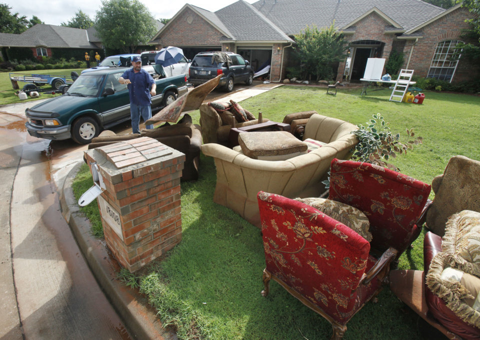 Homeowner Jack Lowry tosses a soaked piece of carpet onto a pile of destroyed furniture at his home at 18108 Vermejo in the Palo Verde addition in Edmond, OK, after yesterday\'s torential rains flooded the neighborhood, Tuesday, June 15, 2010. By Paul Hellstern, The Oklahoman
