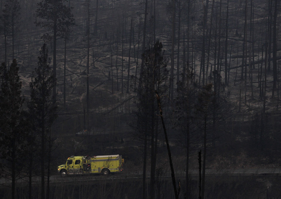 Photo - A fire truck drives past trees burned during the Las Conchas fire in Los Alamos, N.M., Thursday, June 30, 2011.  Global warming is rapidly turning America into a stormy and dangerous place, with rising seas and disasters upending lives from flood-stricken Florida to the wildfire-ravaged West, according to a new U.S. federal scientific report released Tuesday, May 6, 2014. (AP Photo/Jae C. Hong)