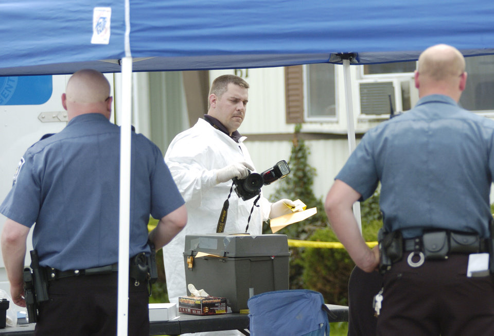 An agent with the Ohio Bureau of Criminal Identification and Investigation, center, works at a crime scene with police officers in Ottawa, Ohio Thursday, May, 9, 2013. Ottawa police said the Thursday morning alert about two missing 17-year-old boys and a missing 14-year-old boy was issued after a mother returned to a Putnam County trailer home and found a crime scene. Police and the sheriff released no details about that scene, the bodies or where they were later found. Autopsies were planned. (AP Photo/The Courier, Randy Roberts)