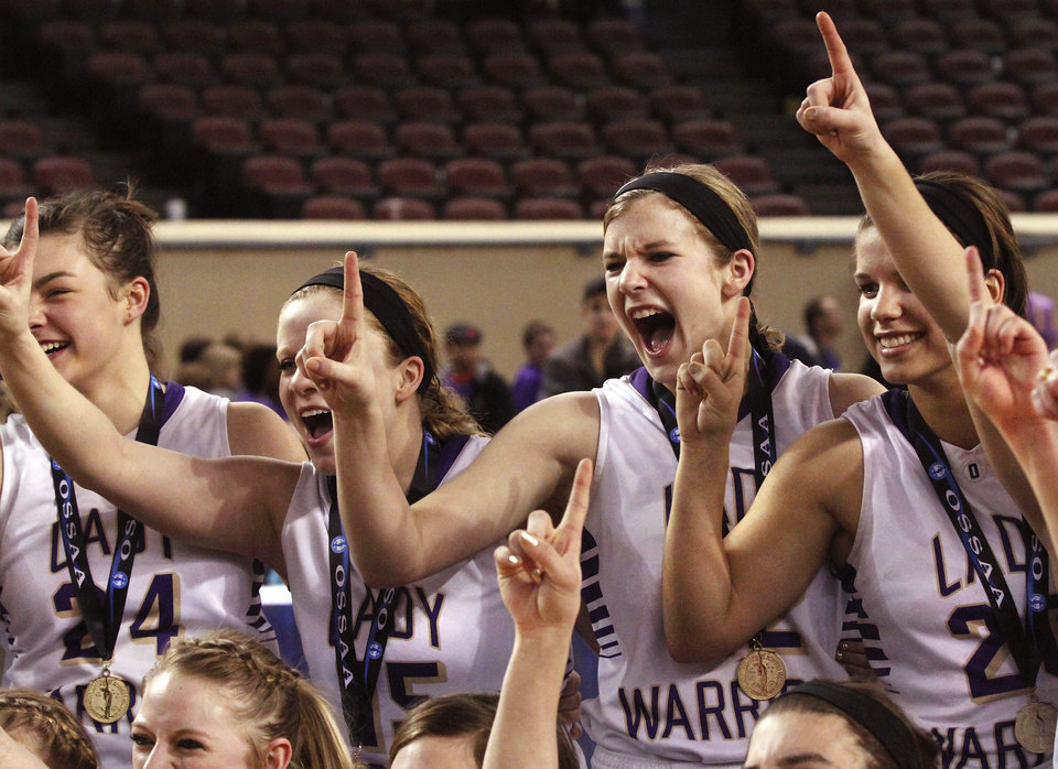 Photo - From left, Madison Lee, Madi Grellner, Kenadey Grellner and Morgan Vogt show that their team is number one while posing for a team photo after awards presentation following the Lady Warriors' win in Class B girls high school basketball championship game in the Jim Norick Arena at State Fair Park on  Saturday, March 8, 2014.   Okarche defeated Red Oak, 66-41. Photo by Jim Beckel, The Oklahoman