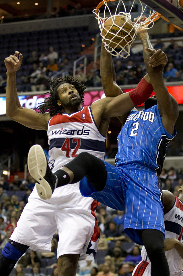 Washington Wizards center Nene (42), of Brazil, guards Orlando Magic power forward Kyle O'Quinn (2) who dunks and scores during the first quarter of an NBA basketball game at the Verizon Center in Washington, Friday, Dec. 28, 2012. (AP Photo/Jacquelyn Martin)