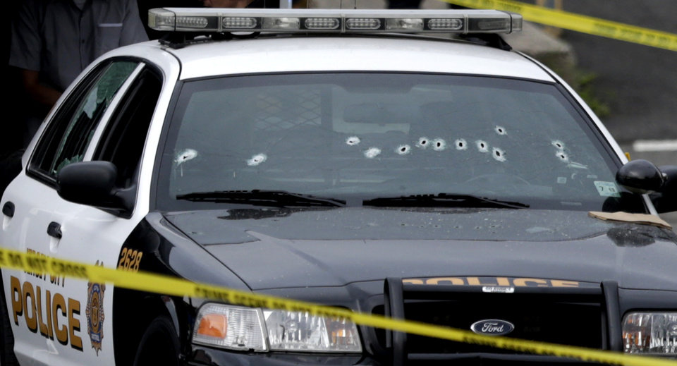 Photo - A Jersey City Police Department cruiser is seen with bullet holes on the windshield at the scene where an officer was shot and killed while responding to a call at a 24-hour pharmacy, Sunday, July 13, 2014, in Jersey City, N.J.  Officer Melvin Santiago was shot in the head while still in his police vehicle as he and his partner responded to an armed robbery call  at about 4.a.m., Jersey City Mayor Steven Fulop said in a statement.  Fulop said officers responding to the robbery call shot and killed the man who shot Santiago. He was not immediately identified. (AP Photo/Julio Cortez)