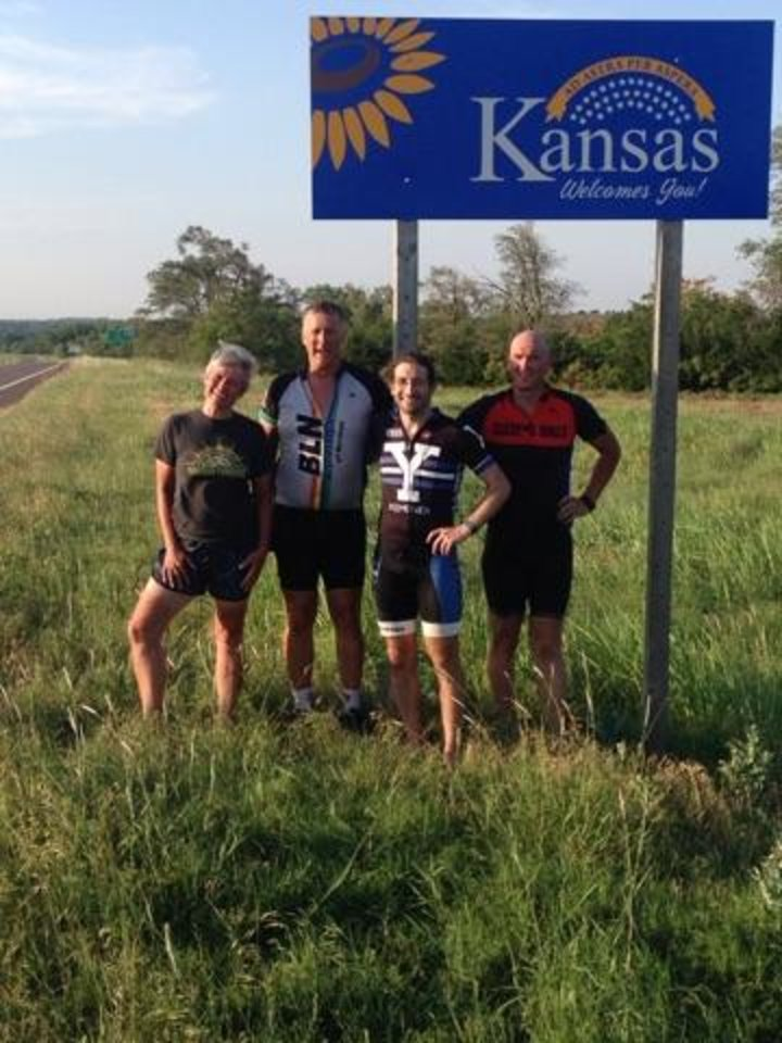 Photo - From left, Daphne Summers, Ron Ponder, Matt Schullman and Jeff Hauser stand on the Kansas border at the end of a long day on their bikes. [Photo Provided]