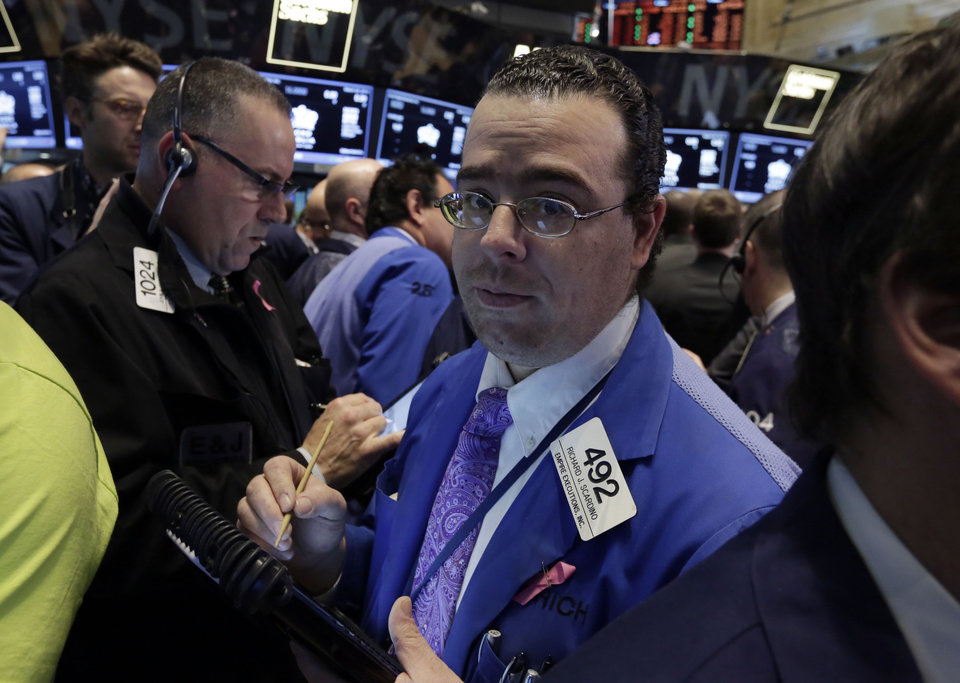 Photo - Trader Richard Scardino, right, works on the floor of the New York Stock Exchange, Wednesday, March 26, 2014.  The stock market opened higher Wednesday after a strong report on American manufacturing. The maker of the hit game