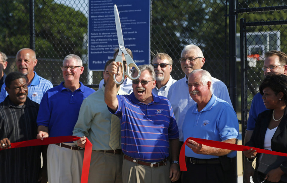 Photo - Midwest City Mayor Jack Fry cuts a ribbon at the new public basketball courts during a grand opening ceremony in Midwest City on Tuesday. The two new courts called Thunder and Rumble replaced a makeshift court and feature new lighting, fencing and the Oklahoma City Thunder logo on soft surface flooring. Photo by Bryan Terry, The Oklahoman  BRYAN TERRY - THE OKLAHOMAN