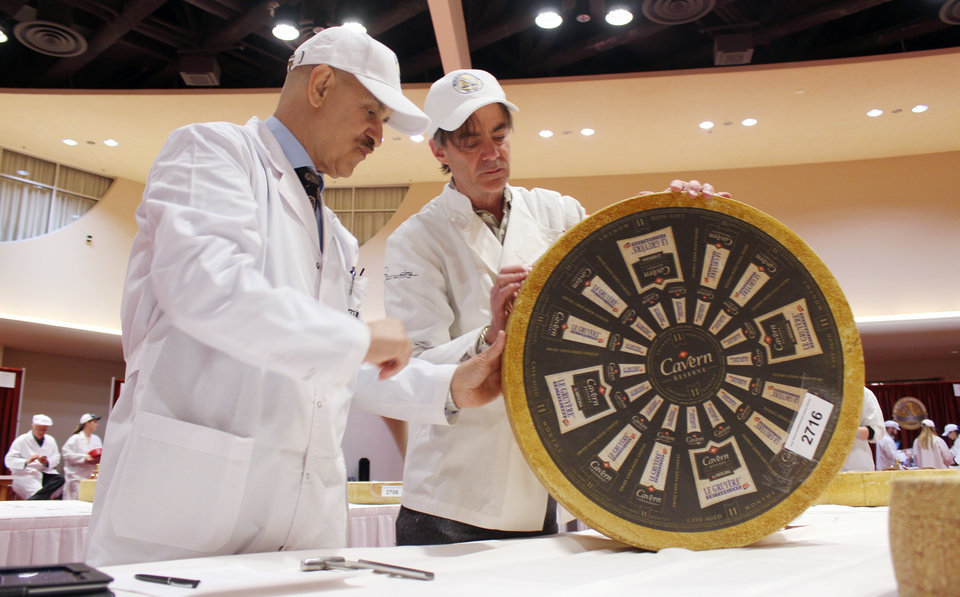 Photo - Roberto Castaneda, left, from Argentina, and Max McCalman inspect a wheel of gruyere during the first day of judging for 2014 World Championship Cheese Contest Tuesday, March 18, 2014, in Madison, Wis. Entries in the 2014 World Championship Cheese Contest reached a new record this year, growing five percent to more than 2,600 entries from 22 nations around the world. (AP Photo/Carrie Antlfinger)