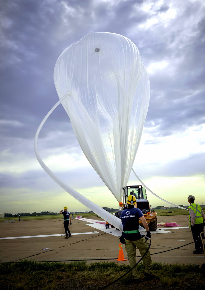 Photo - This photo taken on June 18, 2014, and provided by World View Enterprises, shows the World View team filling a high altitude balloon in Roswell, N.M., for the Voyager pressurized space capsule that will be transported to the edge of space. The Arizona company says it has successfully completed the first scale test flight of a high-altitude balloon and capsule being developed to take tourists to the edge of space. World View Enterprises of Tucson said Tuesday June 24, 2014 that it launched the flight last week from Roswell, NM. CEO Jane Poynter says the system broke the world record for highest parafoil flight, lifting a payload one-tenth of what is planned for passenger flight to 120,000 feet. (AP Photo//World View Enterprises, J. Martin Harris)