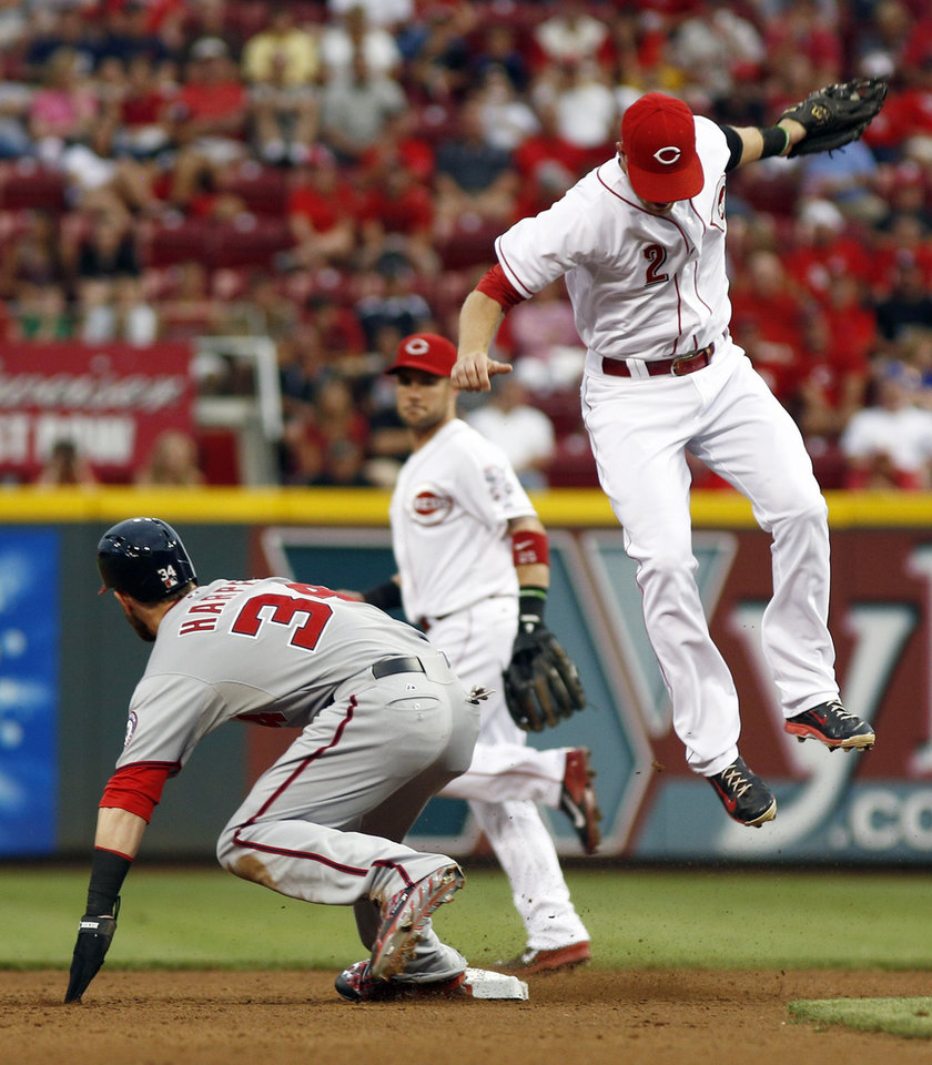 Photo - Washington Nationals' Bryce Harper (34) safely returns to second under Cincinnati Reds shortstop Zack Cozart (2) after a pickoff attempt in the fourth inning of a baseball game, Friday, July 25, 2014, in Cincinnati. (AP Photo/David Kohl)