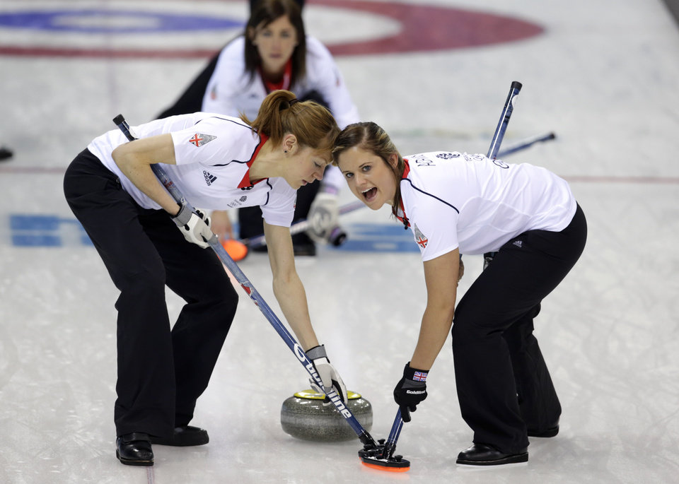 Photo - Britain's Claire Hamilton, left, and Vicki Adams sweep ahead of the stone delivered by skip Eve Muirhead during women's curling competition against Russia at the 2014 Winter Olympics, Monday, Feb. 17, 2014, in Sochi, Russia. (AP Photo/Robert F. Bukaty)