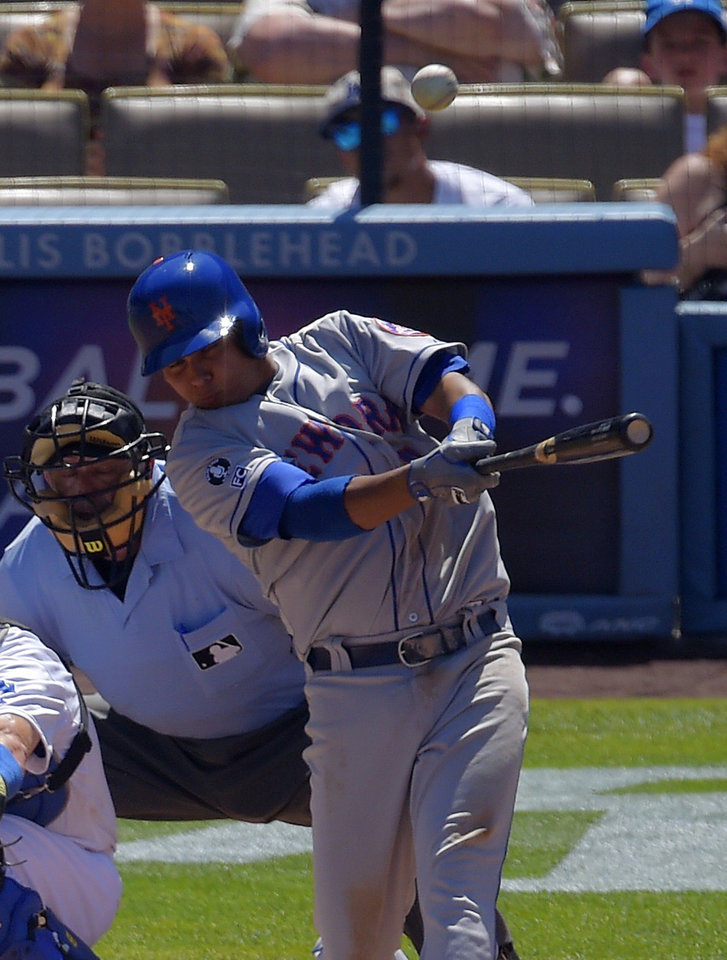 Photo - New York Mets' Ruben Tejada, right, hits a two-run home run as home plate umpire Dale Scott looks on during the third inning of a baseball game against the Los Angeles Dodgers, Sunday, Aug. 24, 2014, in Los Angeles. (AP Photo/Mark J. Terrill)