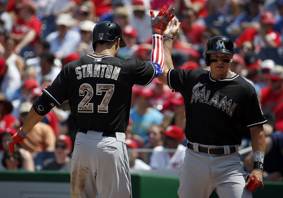 Photo - Miami Marlins' Giancarlo Stanton (27) celebrates his two-run homer with Derek Dietrich, whom he knocked in, during the third inning of a baseball game against the Washington Nationals at Nationals Park Monday, May 26, 2014, in Washington. (AP Photo/Alex Brandon)