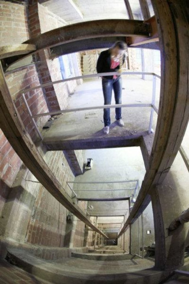 Photo - Oklahoman reporter Amanda Alfanos looks down what was once meant to be an elevator shaft inside the Gold Star Memorial building on the campus of Oklahoma City University in Oklahoma City, OK, Thursday, April 14, 2011. By Paul Hellstern, The Oklahoman ORG XMIT: KOD