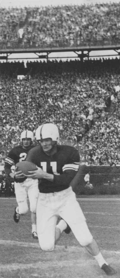 This Sugar bowl action photo shows the University of Oklahoma's Darrell Royal as he picked up nine yards in the first quarter of Monday's Sugar bowl game in New Orleans against Louisiana State. Royal started on the Oklahoma 30-yard line and was halted on the 39 by LSU's Jack Cole, a quarterback. OU won the game, 35-0. Staff Photo by George Tapscott (Published 01/03/1950 in the Oklahoma City Times)