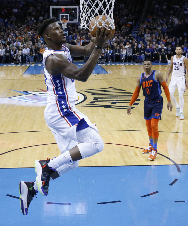 Photo - Philadelphia 76ers guard Jimmy Butler goes up for a shot in front of Oklahoma City Thunder guard Russell Westbrook (0) during the second half of an NBA basketball game Thursday, Feb. 28, 2019, in Oklahoma City. (AP Photo/Sue Ogrocki)