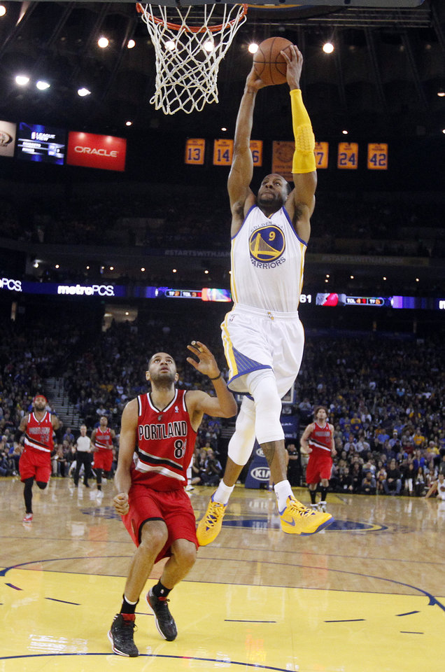 Photo - Golden State Warriors' Andre Iguodala (9) dunks past Portland Trail Blazers' Nicolas Batum during the second half of an NBA basketball game on Sunday, Jan. 26, 2014, in Oakland, Calif. Golden State won 103-88. (AP Photo/Marcio Jose Sanchez)