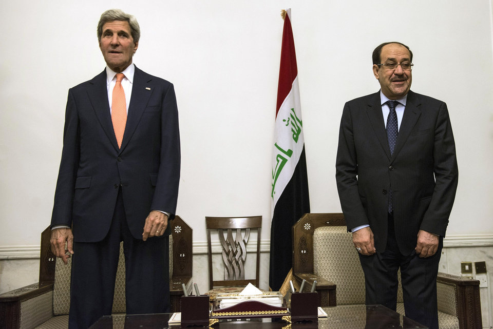 Photo - U.S. Secretary of State John Kerry, left, stands with Iraqi Prime Minister Nouri al-Maliki, right, at the Prime Minister's office in Baghdad on Monday, June 23, 2014. Kerry flew to Baghdad on Monday to meet with Iraq's leaders and personally urge the Shiite-led government to give more power to political opponents before a Sunni insurgency seizes more control across the country and sweeps away hopes for lasting peace. (AP Photo/Brendan Smialowski, Pool)