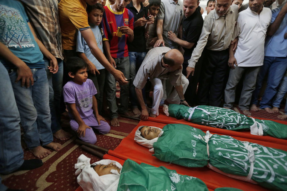 Photo - Palestinian mourners gather around the bodies of three siblings of the Abu Musallam family, during their funeral in Beit Lahiya, northern Gaza Strip, Friday, July 18, 2014. Ismail Abu Musallam, the father of the children said that Ahmed, 11, Walaa, 14 and Mohammed,16, were sleeping when the shell struck the family home, and that he had to dig them out of the rubble. (AP Photo/Lefteris Pitarakis)