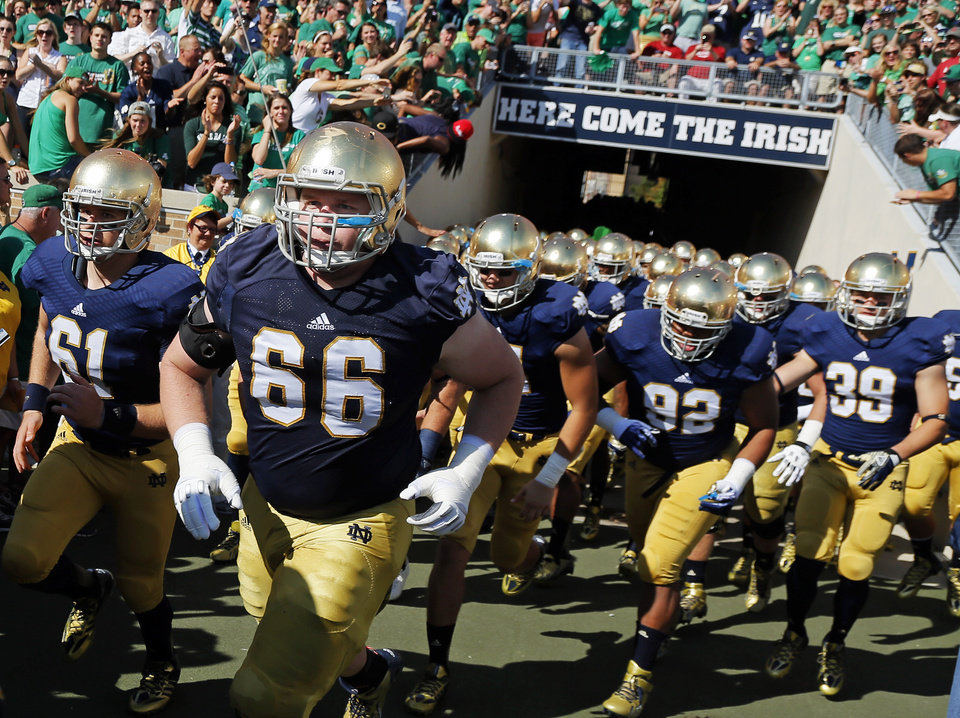 Photo - Notre Dame takes the field during a college football game between the University of Oklahoma Sooners (OU) and the Notre Dame Fighting Irish at Notre Dame Stadium in South Bend, Ind., Saturday, Sept. 28, 2013. Photo by Nate Billings, The Oklahoman