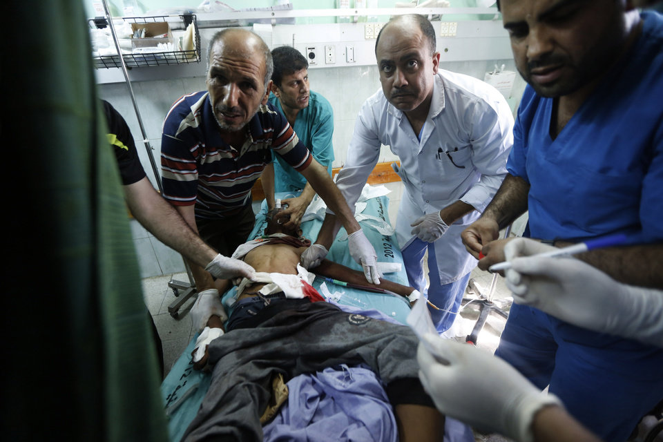 Photo - Palestinian medics treat a child wounded in an Israeli strike on a compound housing a U.N. school in Beit Hanoun, in the northern Gaza Strip, at the emergency room of the Kamal Adwan hospital in Beit Lahiya, Thursday, July 24, 2014. Israeli tank shells hit the compound, killing more than a dozen people and wounding dozens more who were seeking shelter from fierce clashes on the streets outside. Gaza health official Ashraf al-Kidra says the dead and injured in the school compound were among hundreds of people seeking shelter from heavy fighting in the area. (AP Photo/Lefteris Pitarakis)