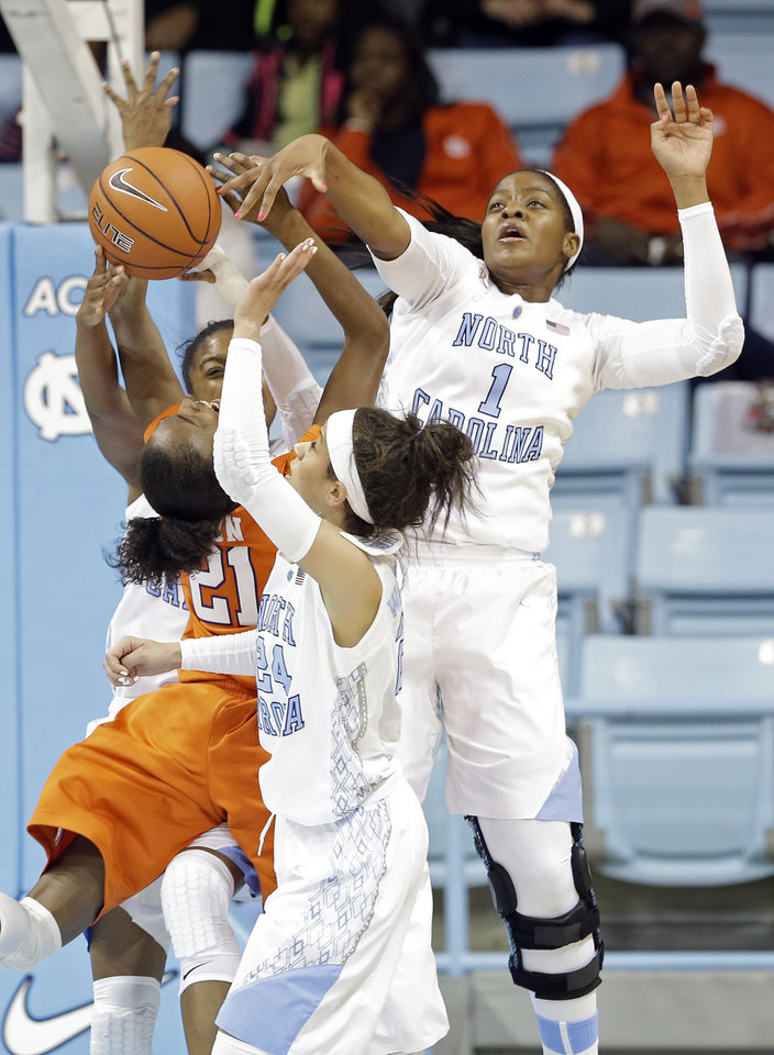 Photo - North Carolina's Stephanie Mavunga (1) and Jessica Washington (24) defend against Clemson's Nikki Dixon (21) during the first half of an NCAA college basketball game in Chapel Hill, N.C., Thursday, Jan. 16, 2014. (AP Photo/Gerry Broome)