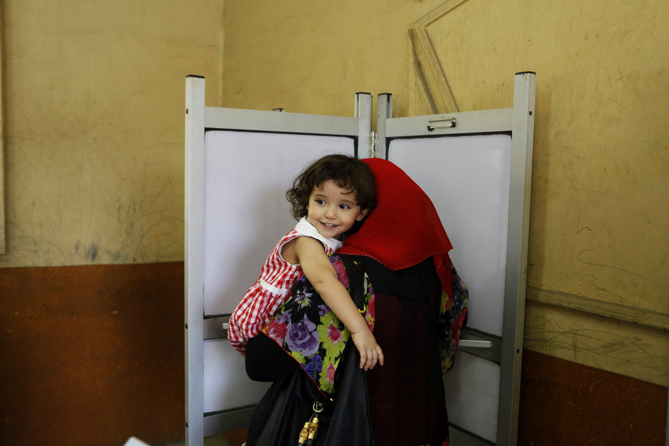 Photo -   An Egyptian woman carries her daughter as she votes at a polling station during the second day of the presidential runoff, in Cairo, Egypt, Sunday, June 17, 2012. Egyptians are choosing between a conservative Islamist and Hosni Mubarak's ex-prime minister in a second day of a presidential runoff that has been overshadowed by the domination of the country's military. (AP Photo/Amr Nabil)
