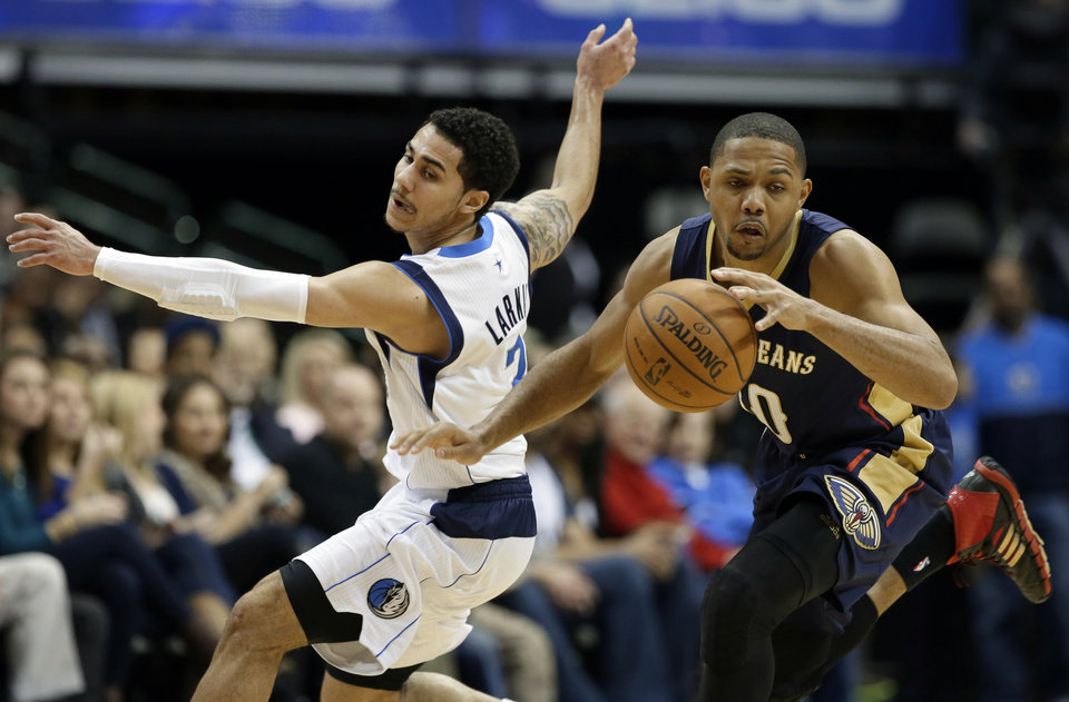 Photo - New Orleans Pelicans' Eric Gordon (10) grabs a loose ball in front of Dallas Mavericks' Shane Larkin, left, in the first half of an NBA basketball game, Saturday, Jan. 11, 2014, in Dallas. (AP Photo/Tony Gutierrez)