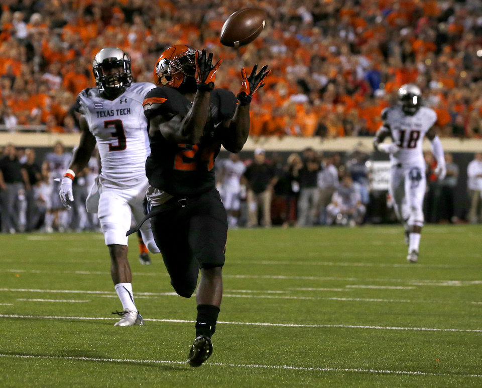 Photo - Oklahoma State's Tyreek Hill (24) catches a touchdown pass on front of Texas Tech's J.J. Gaines (3) during a college football game between the Oklahoma State Cowboys (OSU) and the Texas Tech Red Raiders at Boone Pickens Stadium in Stillwater, Okla., Thursday, Sept. 25, 2014. Photo by Bryan Terry, The Oklahoman